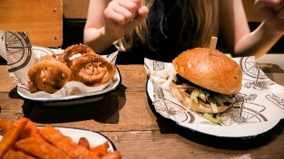Meal at Top Dog Soho including, burger, sweet potato fries and onion rings