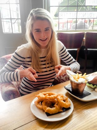 Woman Smiling and pointing at Onion Rings at The Orange Tree Pub Richmond