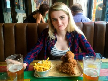 Woman with beer, chicken and chips
